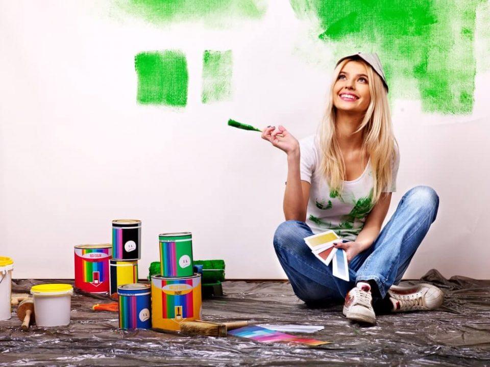 Woman paint wall at home