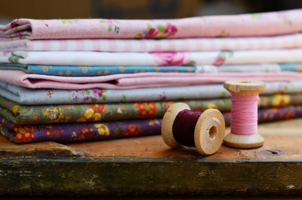 Set of different fabrics and wooden thread spools