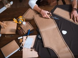 Cropped shot of male fashion designer working with sewing patterns, tools and fabric at workplace