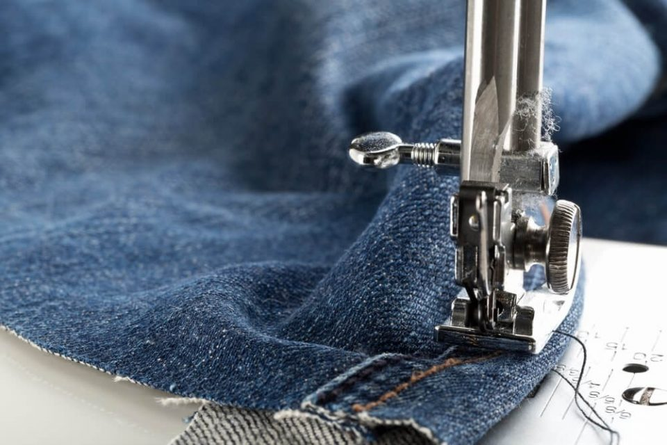 Blue jeans denim sewed on sewing machine close up - jeans fashion mending or repair concept, selective focus