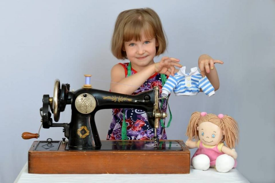 Child, kid,(little girl) seamstress sews clothes for the dolls on the old sewing machine