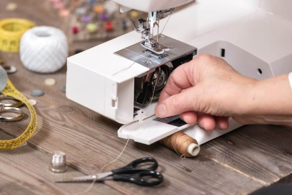 Close-up of senior woman seamstress hands removing the bobbin case in order to do the maintenance of a electrical sewing machine