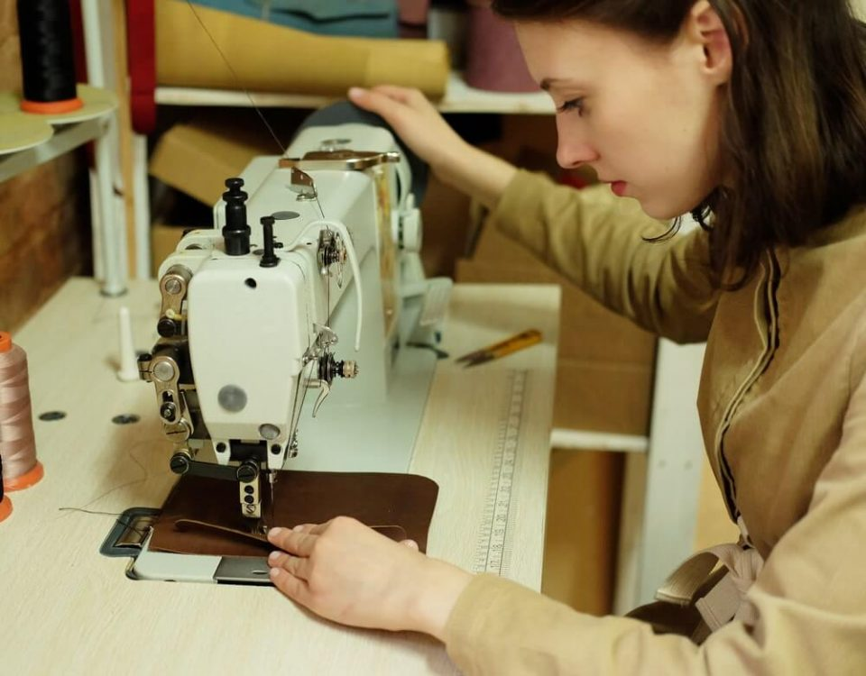 Closeup on young woman sewing leather handbag