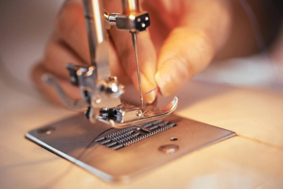 Closeup shot of hand of anonymous tailor putting thin thread in needle of modern sewing machine in workshop
