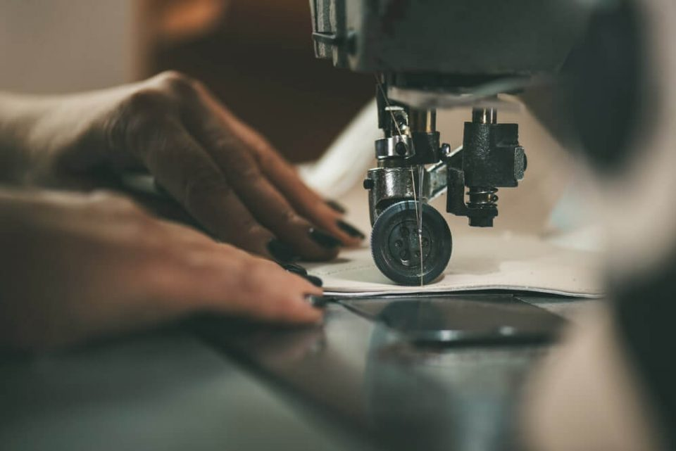 Cropped shot of seamstress working with sewing machine