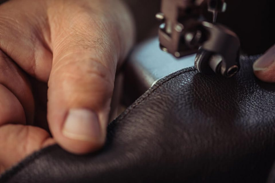 Cropped view of cobbler sewing genuine leather on sewing machine