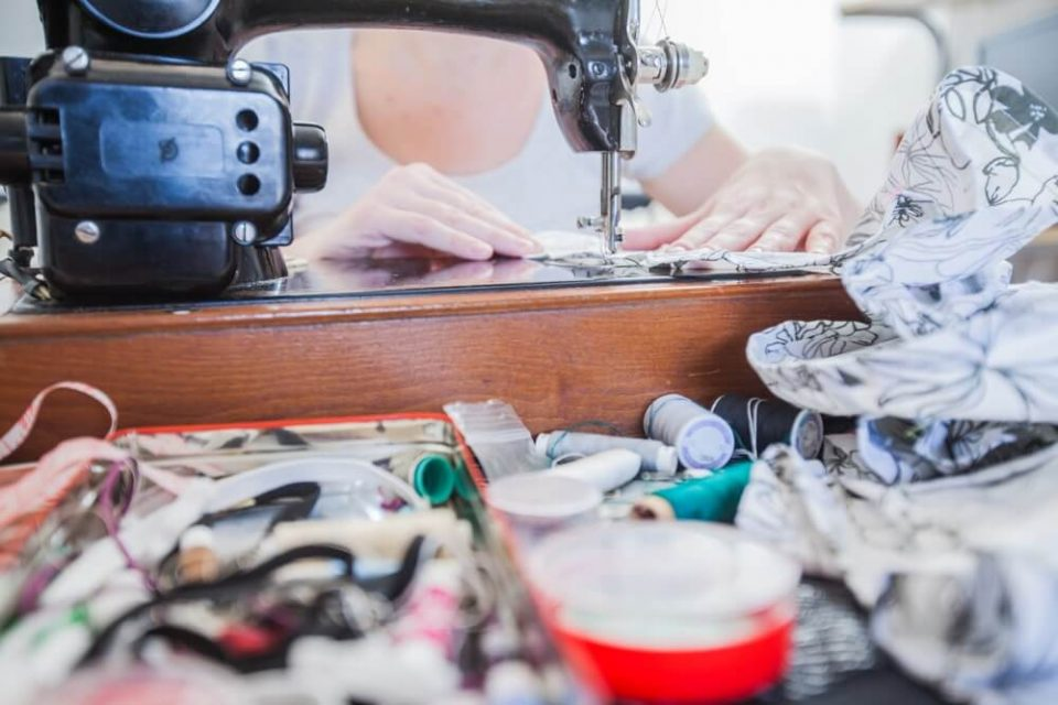 Female tailor hands using retro sewing machine for making dress at home