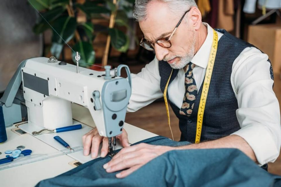 Handsome tailor in glasses sewing cloth with sewing machine at sewing workshop