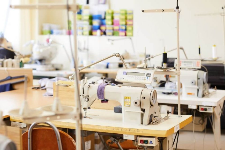 Modern sewing machines on work places in workshop