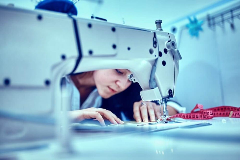 Sewing dress on the sewing machine close-u