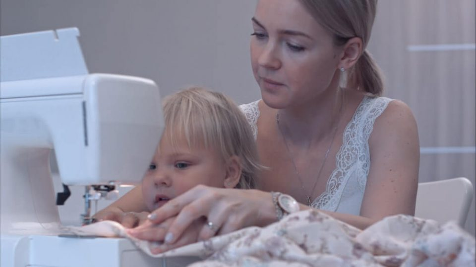 Small child learns new knowledge with her mother using sewing machine